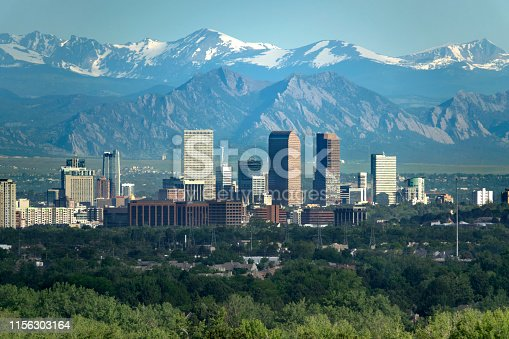 The snow covered Rocky Mountains and Indian Peaks rise over wind turbines, Boulder Flatirons and Downtown Denver skyscrapers, hotels, office and apartment buildings.