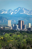 The snow covered Rocky Mountains and Longs Peak rises over the Boulder Flatirons and Downtown Denver skyscrapers, hotels, office and apartment buildings.