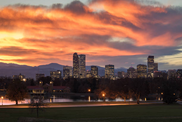 Denver Colorado skyline during sunset, with the Rocky Mountains visible in the background