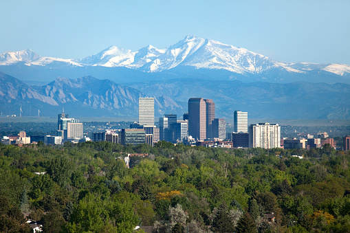 Snow covered Longs Peak, part of the Rocky Mountains stands tall in the background with green trees and the Downtown Denver skyscrapers as well as hotels, office buildings and apartment buildings filling the skyline.