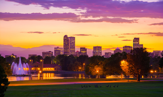 Downtown Denver skyline at sunset with City Park, including a lake, fountains, and a group of geese in the foreground and the Rocky Mountains and clouds in the background.