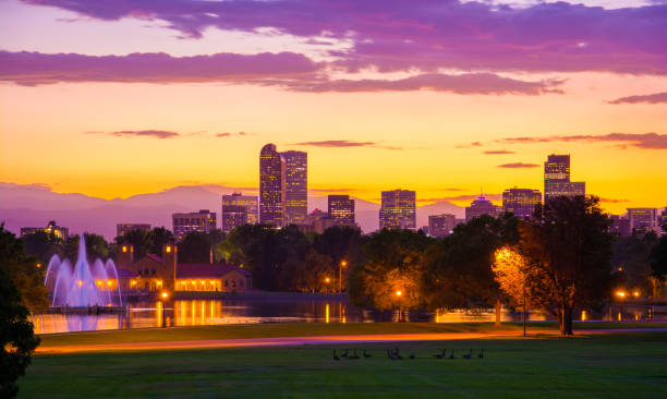Denver skyline at sunset with fountains, lake, mountains, and geese Downtown Denver skyline at sunset with City Park, including a lake, fountains, and a group of geese in the foreground and the Rocky Mountains and clouds in the background. denver stock pictures, royalty-free photos & images