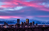 Photography of the Denver Skyline at Sunset with snowy winter peaks in distance.