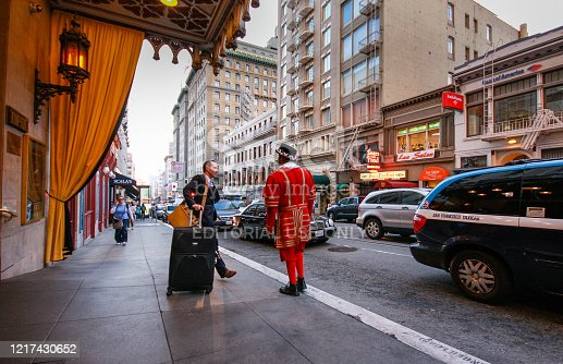 San Francisco, USA - Oct 2, 2012: A departing guest of Kimpton Sir Francis Drake hotel asks a doorman in a beefeater suit to call him a taxi on Oct 2, 2012 in San Francisco, USA.