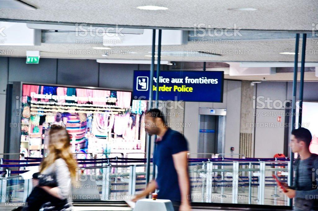 Avgaendenyanlanda Passagerare Gar Forbi En Grans Polis Skylt Frankrike Foton Och Fler Bilder Pa Affischtavla Istock