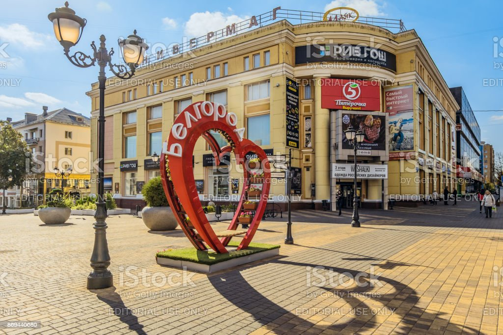 Department Store ' Lighthouse '. Pedestrian street in the old residential center of the city. Bench of love in the shape of a heart with flower pots. Belgorod, Russia. stock photo