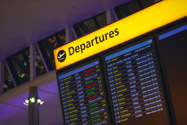 Departure board displaying flight information at departure hall of London Heathrow airport stock photo