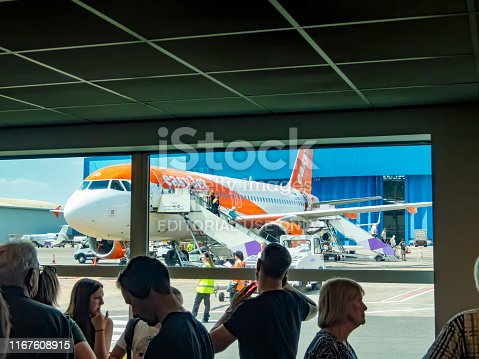 Luton, UK. Departure lounge at Luton Airport with franchises in the background selling food and groups of travellers in the foreground waiting for flight information on the departure screens.