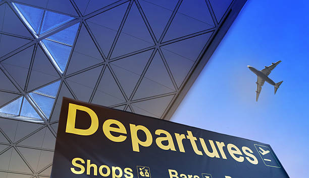 Departure sign in airport Departure sign in airport against of blue sky and plane in the sky arrival departure board stock pictures, royalty-free photos & images