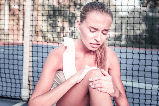 deplorable dissatisfied female player having sport trauma - deplorable stock pictures, royalty-free photos & images