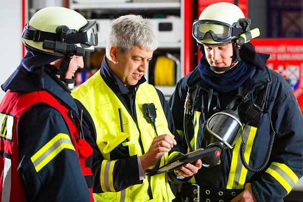 deployment planning on tablet-computer - firefighter stock photos and pictures
