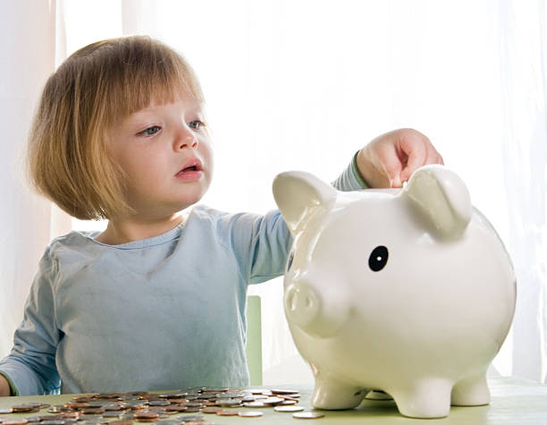 deposit little girl depositing change in her piggy bank allowance stock pictures, royalty-free photos & images