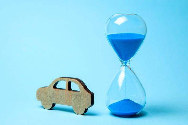 Depreciation or depreciation of the car over time. Wooden car and hourglass on blue background. Old car, second hand repair. Depreciation or depreciation of the car over time. Wooden car and hourglass on blue background. Old car, second hand repair depreciation stock pictures, royalty-free photos & images