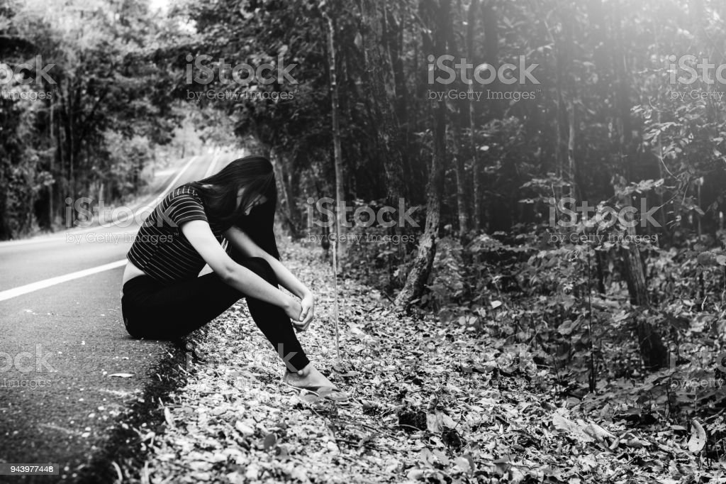 depress and hopeless , Asian woman sitting on roadside, waiting for help stock photo