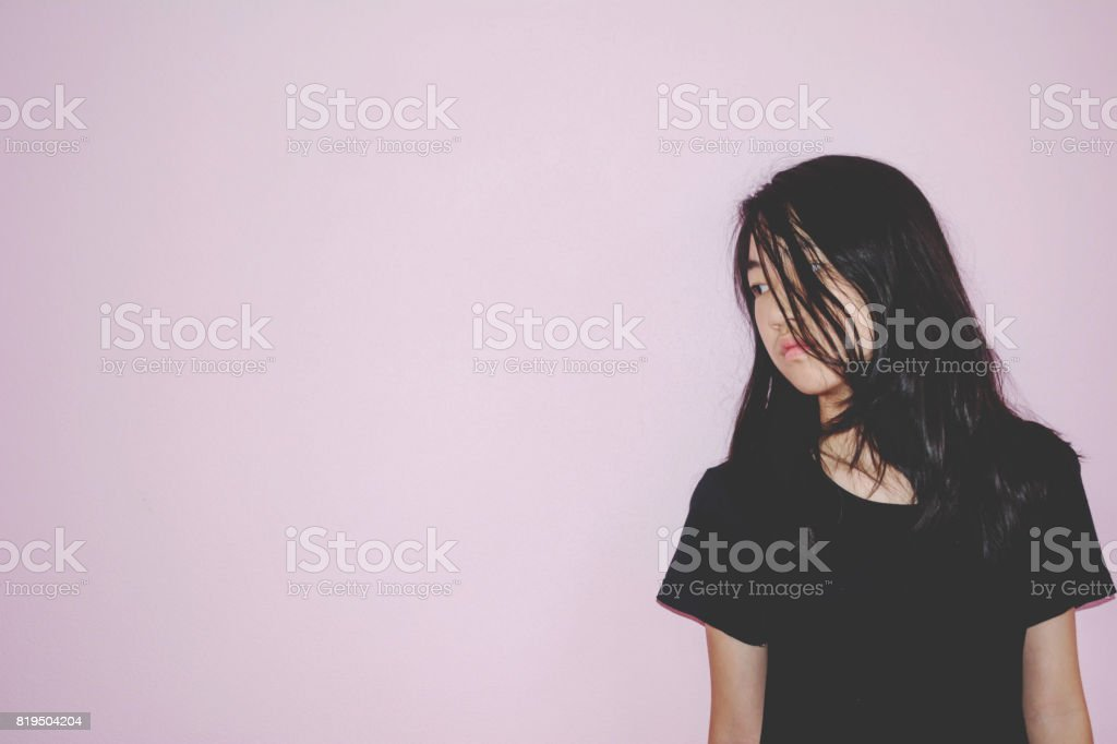 depress and hopeless girl with absent minded looking down stand on pink background stock photo