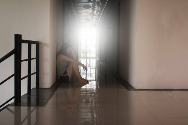 depress and hopeless woman sitting in the dark at corrido - human trafficking stock photos and pictures