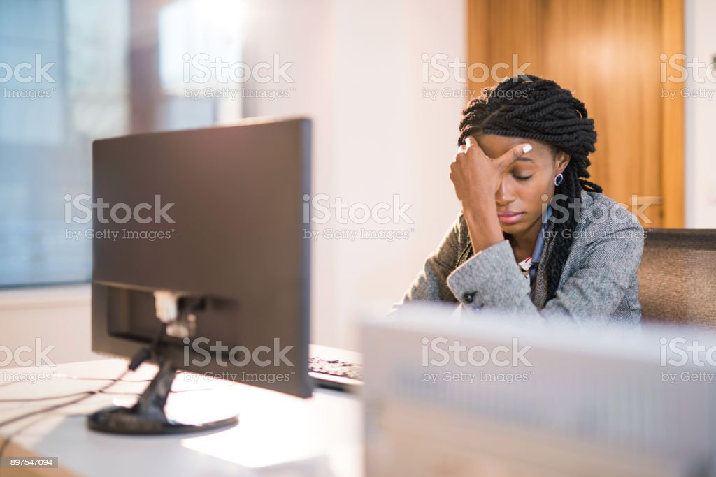 Depressed African woman at work. stock photo