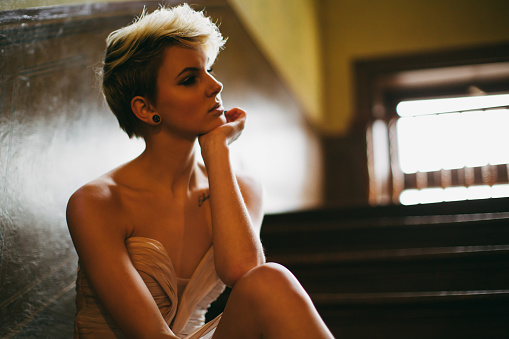 Depressed and angry blonde young woman waering an evening gown sitting on wooden stairway steps of old mansion. Woman Angry - Sadness - Depression Concept.