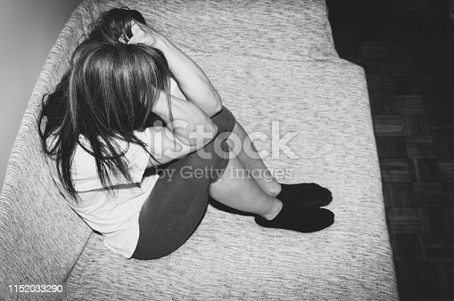 Depressed and lonely girl abused as young sitting alone in her room on the bed feeling miserable and anxiety cry over her life, dark image black and white hard contrast