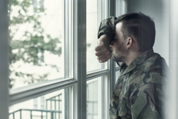 Depressed and sad soldier in green uniform with trauma after war standing near the window Depressed and sad soldier in green uniform with trauma after war standing near the window post traumatic stress disorder stock pictures, royalty-free photos & images