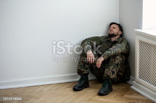 istock Depressed army man in uniform sitting in a corner of an empty room. Place for your poster on the wall 1014213044
