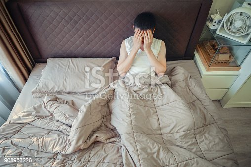 istock Depressed Asian man blaming on the phone on bed 908953226