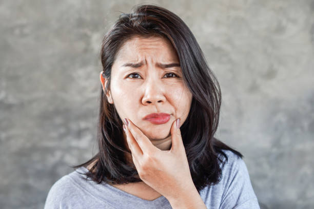 depressed Asian woman having problem with Bell's Palsy/Facial Palsy, hand holding her face depressed Asian woman having problem with Bell's Palsy/Facial Palsy, hand holding her face paralysis stock pictures, royalty-free photos & images