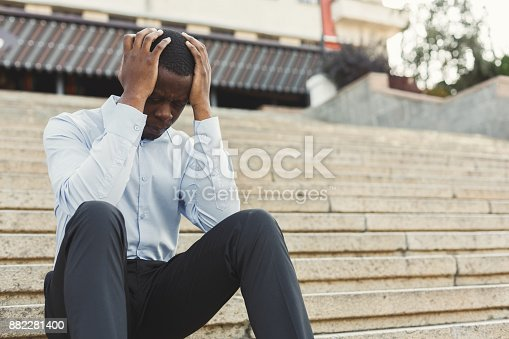 Desperate black businessman with hands on head sitting on concrete stairs in urban city area. Emotional pain, sadness, business problems and depression concept