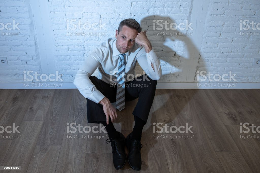 depressed business man feeling sad, lonely and suffering from anxiety leaning on a white wall at home in mental health depression concept royalty-free stock photo