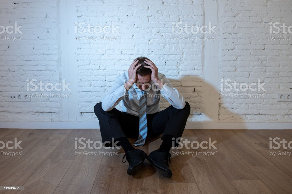 depressed business man feeling sad, lonely and suffering from anxiety leaning on a white wall at home in mental health depression concept zbiór zdjęć royalty-free
