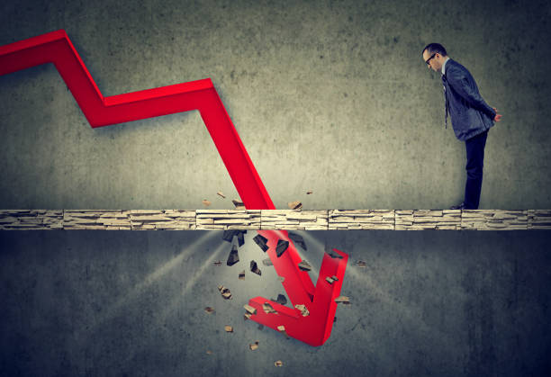 Depressed business man looking down at the falling red arrow going through a concrete floor. Fall and depreciation concept. Curious worried business man looking down at the falling red arrow going through a concrete floor. depreciation stock pictures, royalty-free photos & images