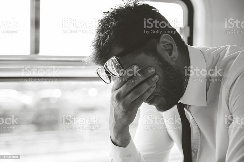 Depressed business man traveling home by train stock photo