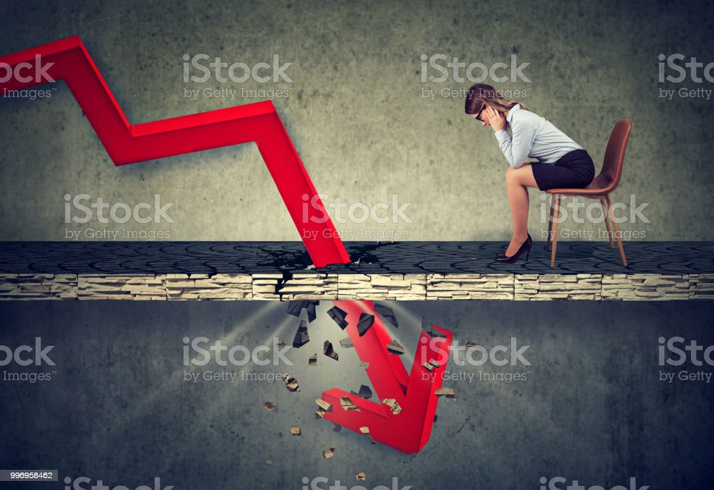 Depressed business woman looking down at the falling red arrow stock photo