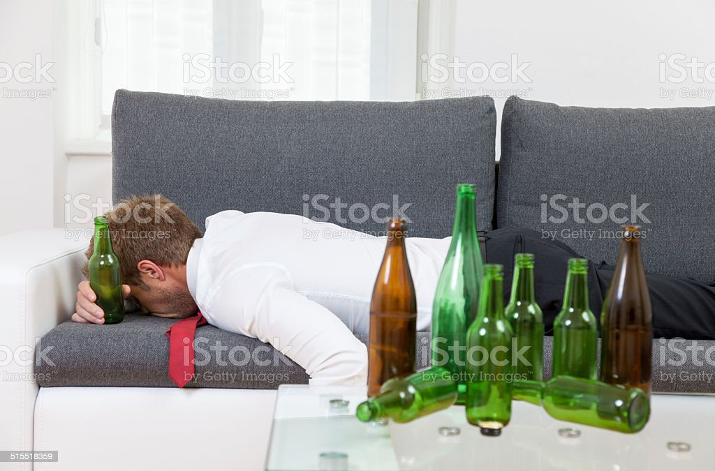 Depressed businessman drunk at home stock photo