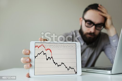 istock Depressed businessman leaning head below bad stock market chart 465702456