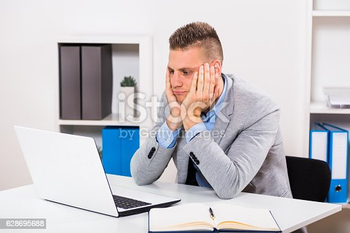 istock Depressed businessman looking at laptop 628695688