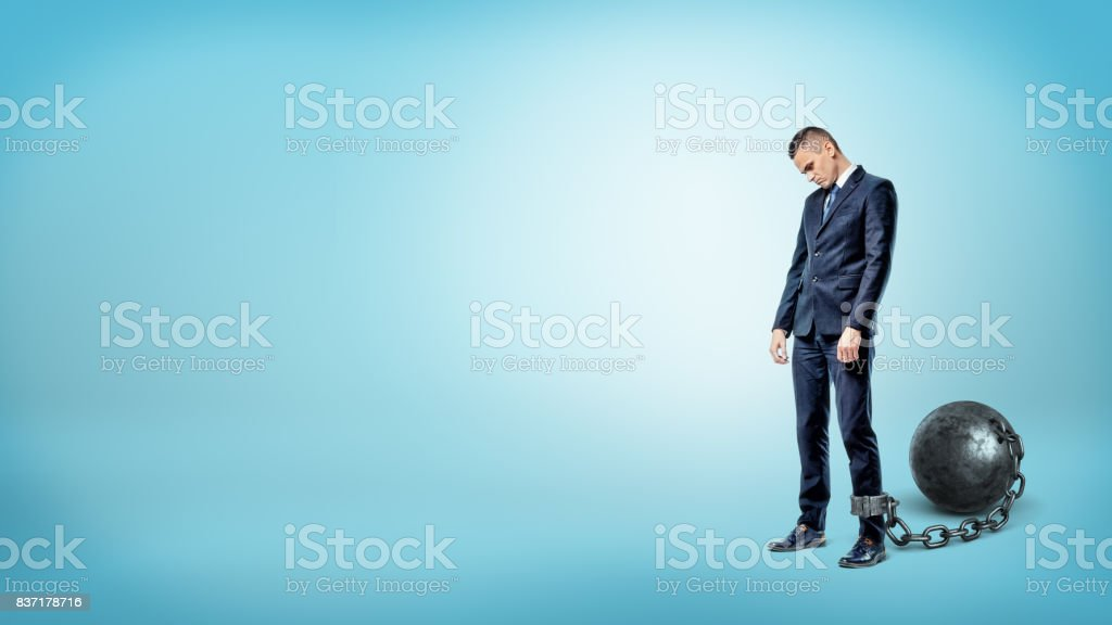 A depressed businessman on blue background stands with a lowered head while chained to an iron ball stock photo
