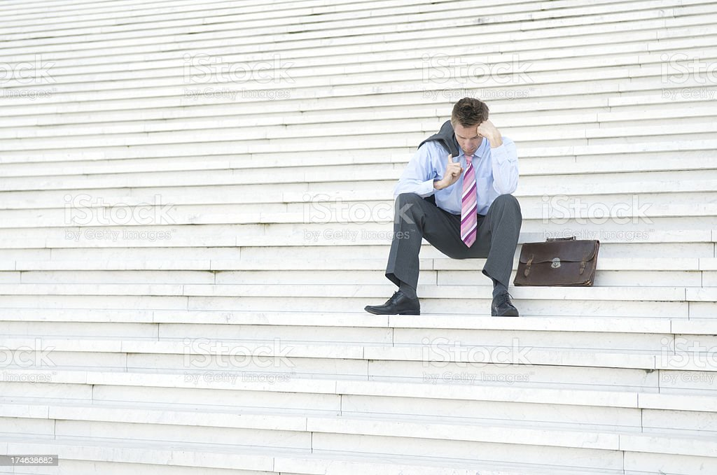 Depressed Businessman Sitting Alone on White Steps Looking Down royalty-free stock photo