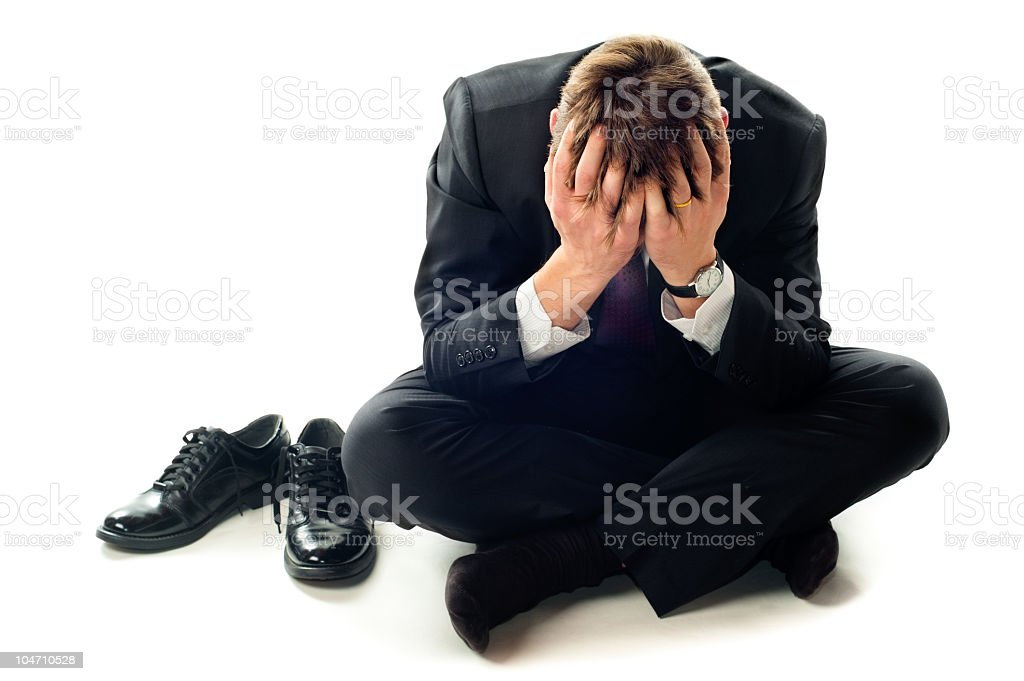 Depressed businessman sitting on floor with head in hands royalty-free stock photo