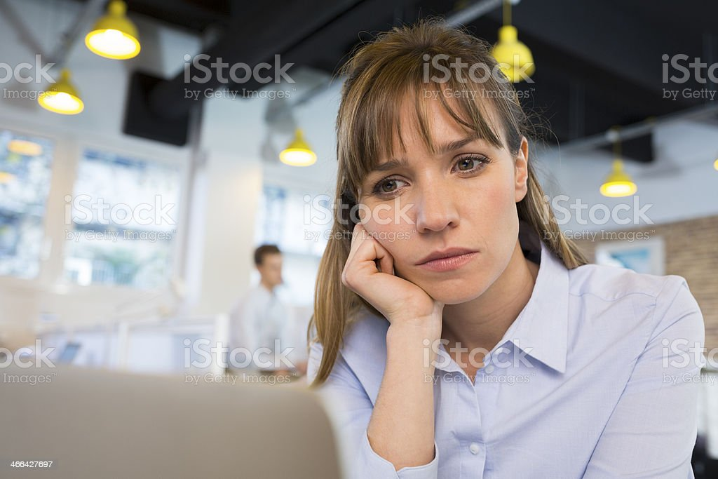 Depressed businesswoman in office behind her laptop stock photo
