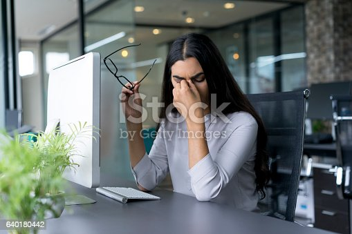 istock Depressed businesswoman rubbing eyes in office 640180442