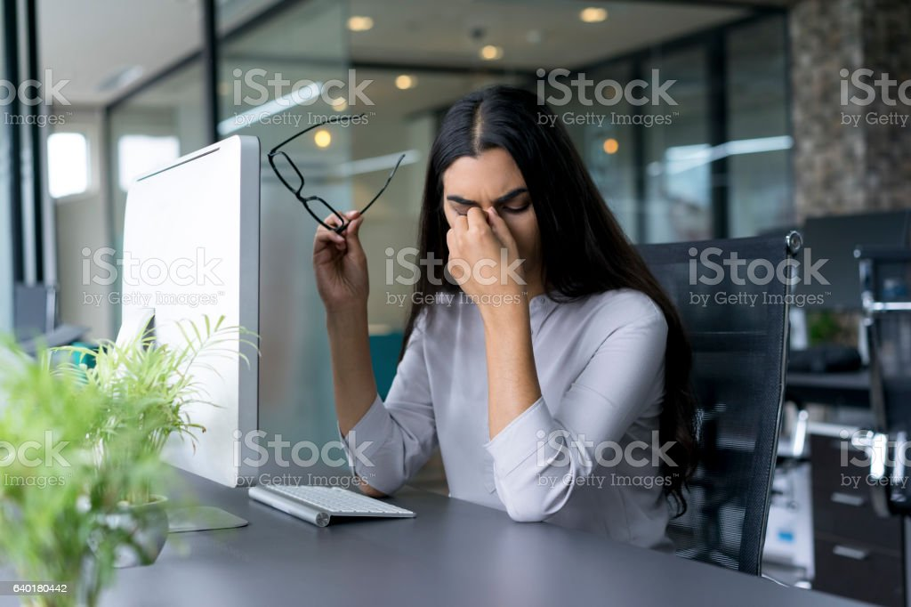 Depressed businesswoman rubbing eyes in office stock photo