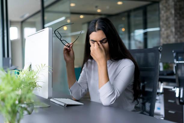 Depressed businesswoman rubbing eyes in office - foto de acervo