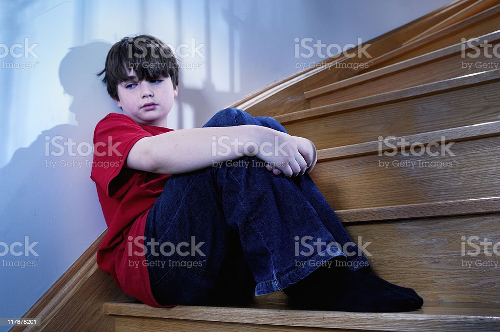 Depressed child sitting on staircase stock photo