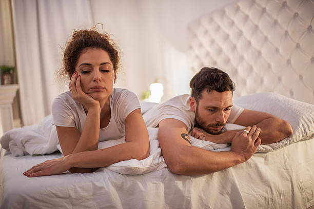 Depressed couple having relationship problems in their bed. stock photo