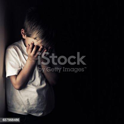 Depressed 6 years old child crying. Dark background.