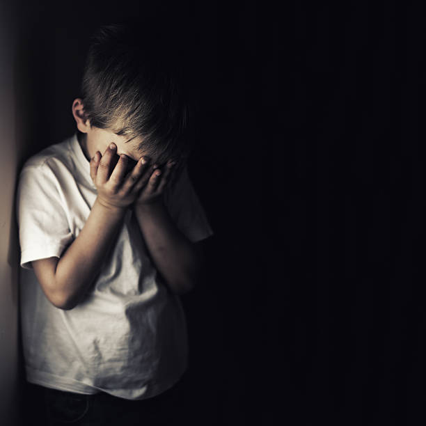 Depressed Crying Little Boy Holding Head In Hands Stock Photo