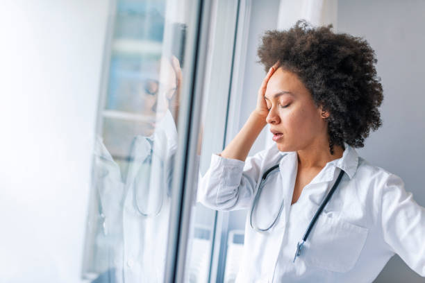 Depressed doctor Nurse doctor with migraine overworked, overstressed isolated background hospital hall corridor. Tired female doctor near window in hospital. It's a stressful profession mental burnout stock pictures, royalty-free photos & images