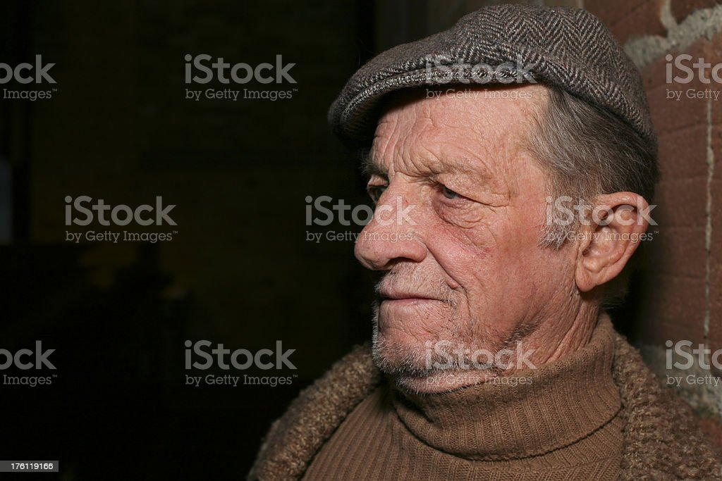 Depressed Elderly Man Leaning on a Brick Wall stock photo