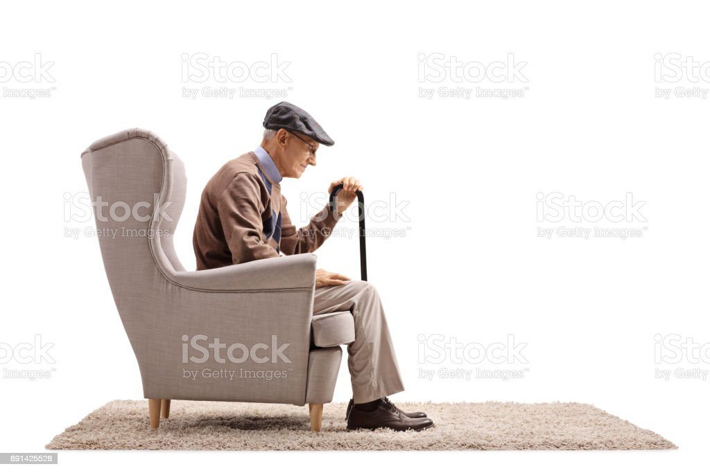 Depressed elderly man seated in an armchair stock photo